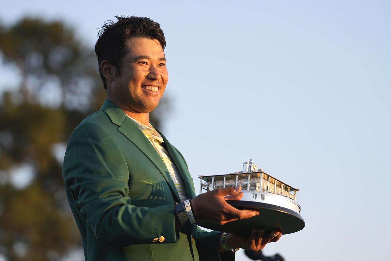 米ゴルフのマスターズ・トーナメントで、日本男子初のメジャー制覇を果たし、トロフィーを手に笑顔の松山(AP)