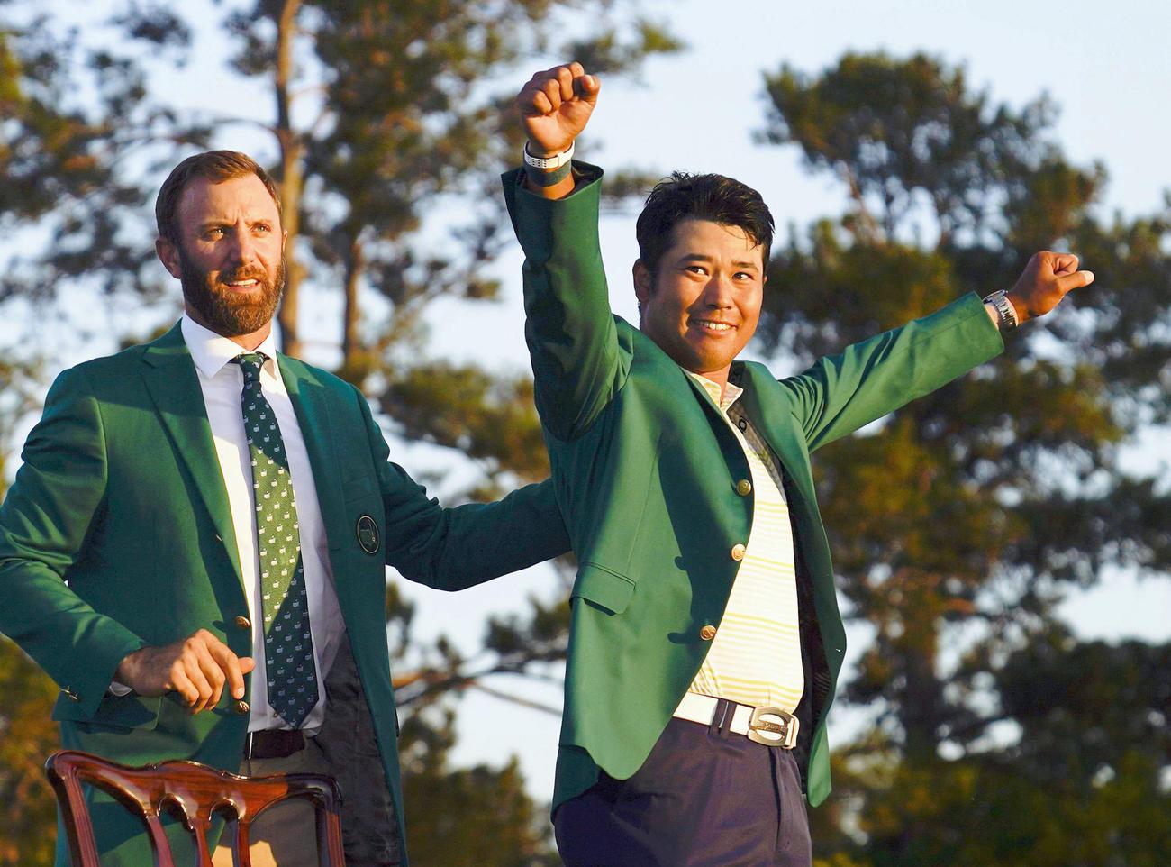米ゴルフのマスターズ・トーナメントで日本男子初のメジャー制覇を果たし、グリーンジャケットを着て喜ぶ松山英樹。左は前年優勝のダスティン・ジョンソン(AP=共同)