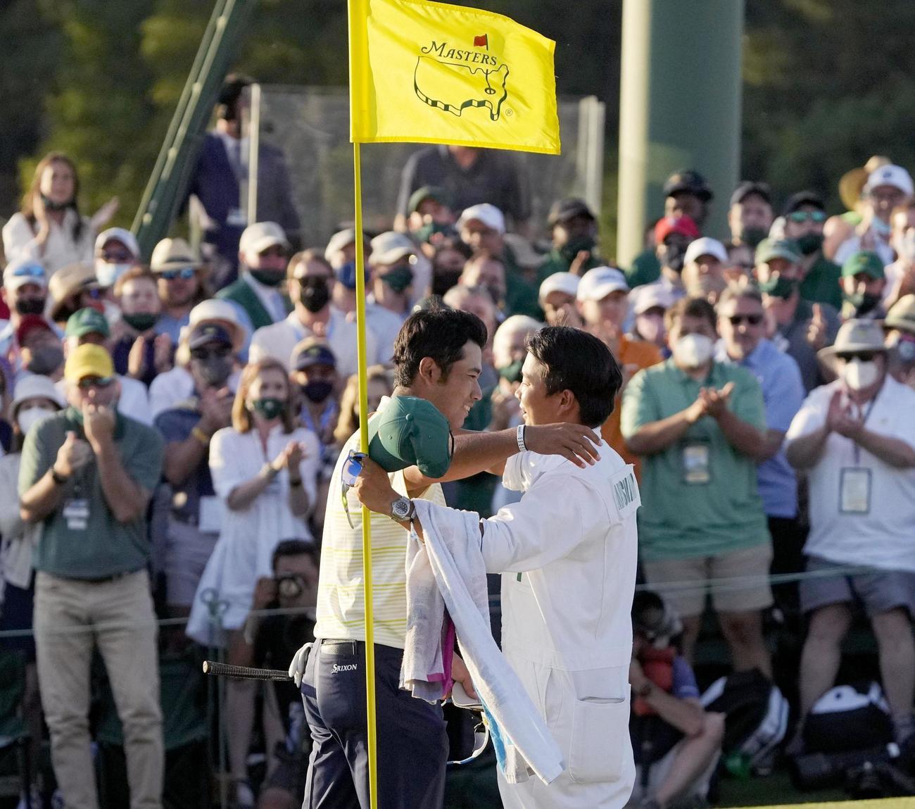 米ゴルフのマスターズ・トーナメントで、日本男子初のメジャー制覇を果たし、キャディー(手前右)と抱き合う松山英樹(AP=共同)