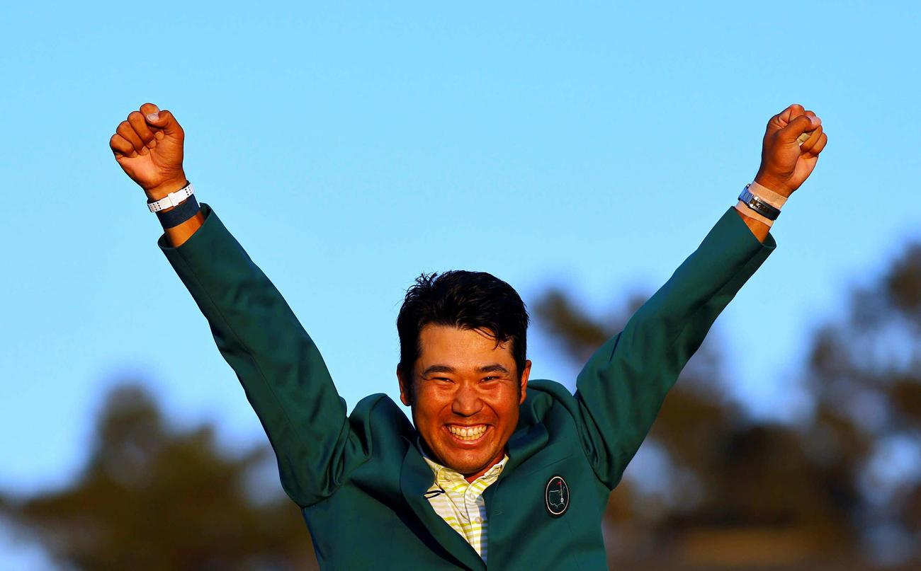 米ゴルフのマスターズ・トーナメントで、日本男子初のメジャー制覇を果たし、グリーンジャケットを着て両手を上げる松山(ロイター)