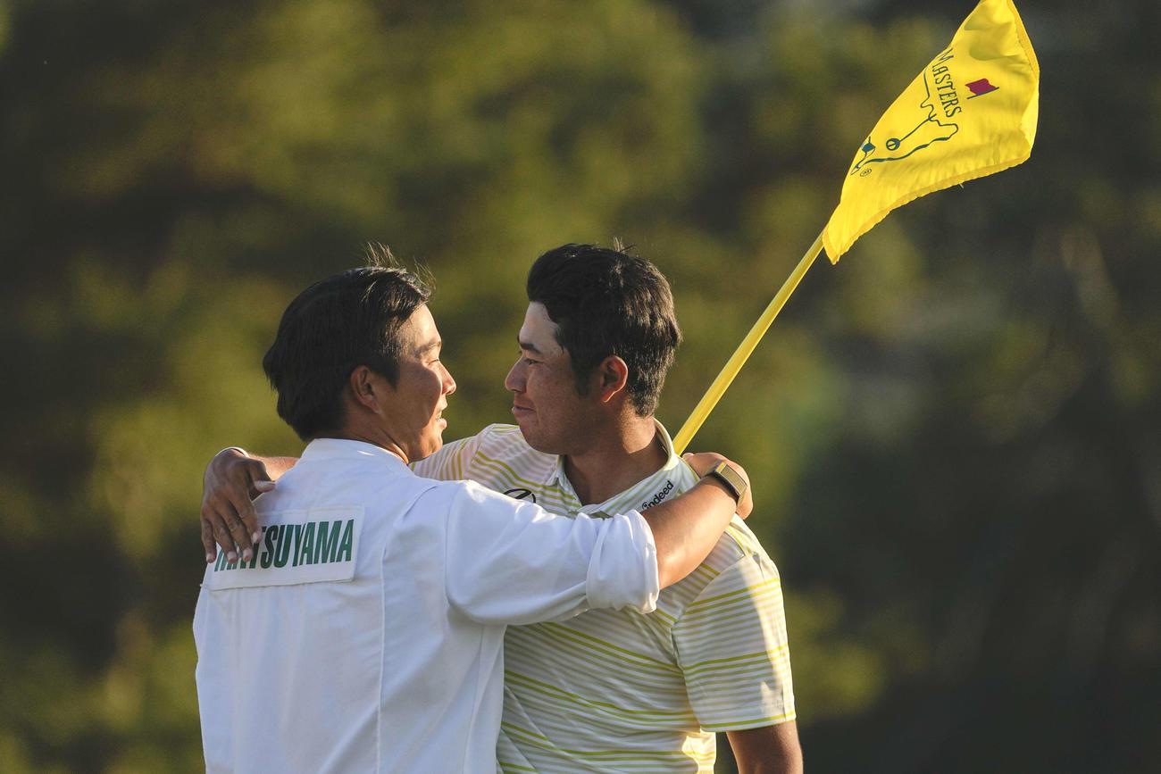 マスターズを制した松山(右)は早藤キャディーと抱き合って喜ぶ(AP)