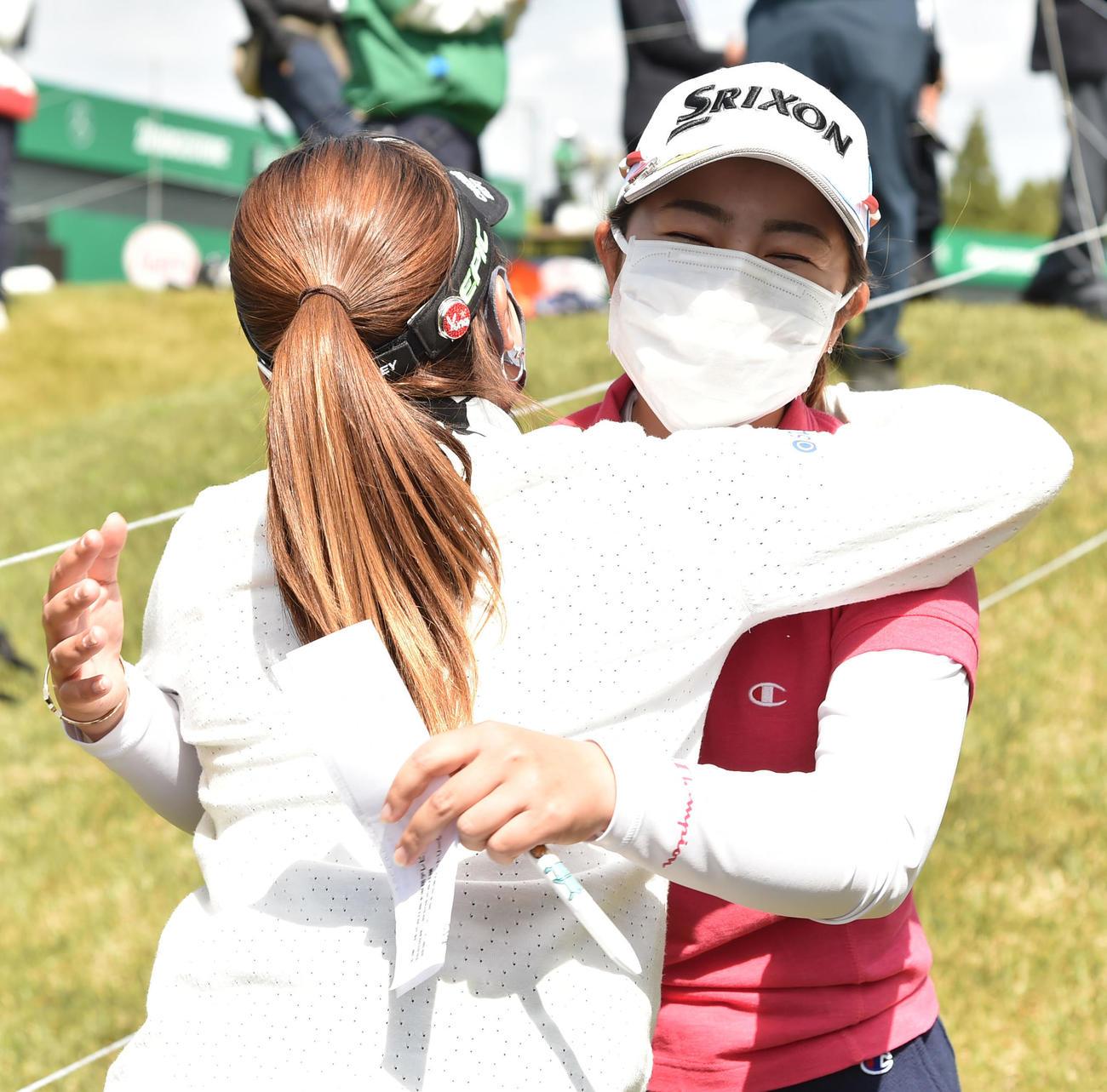 ツアー初優勝を決め、西村(左)から祝福され笑顔を見せる山下(撮影・岩下翔太)