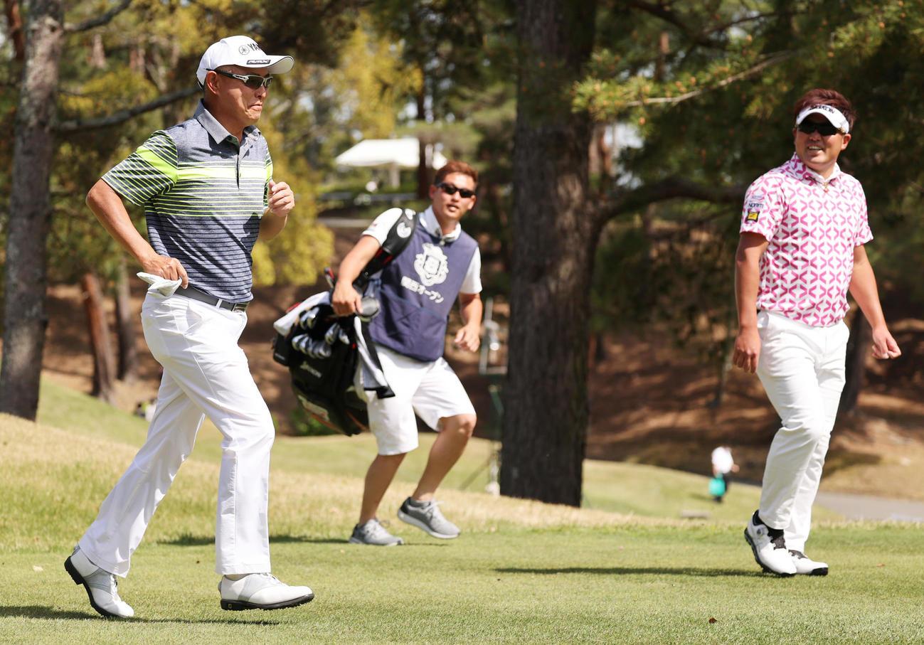 関西オープンゴルフ選手権第1日 1番、ティーショットを放ち、元気に駆け出す谷口(左)に秋吉(右)も笑顔(撮影・清水貴仁)