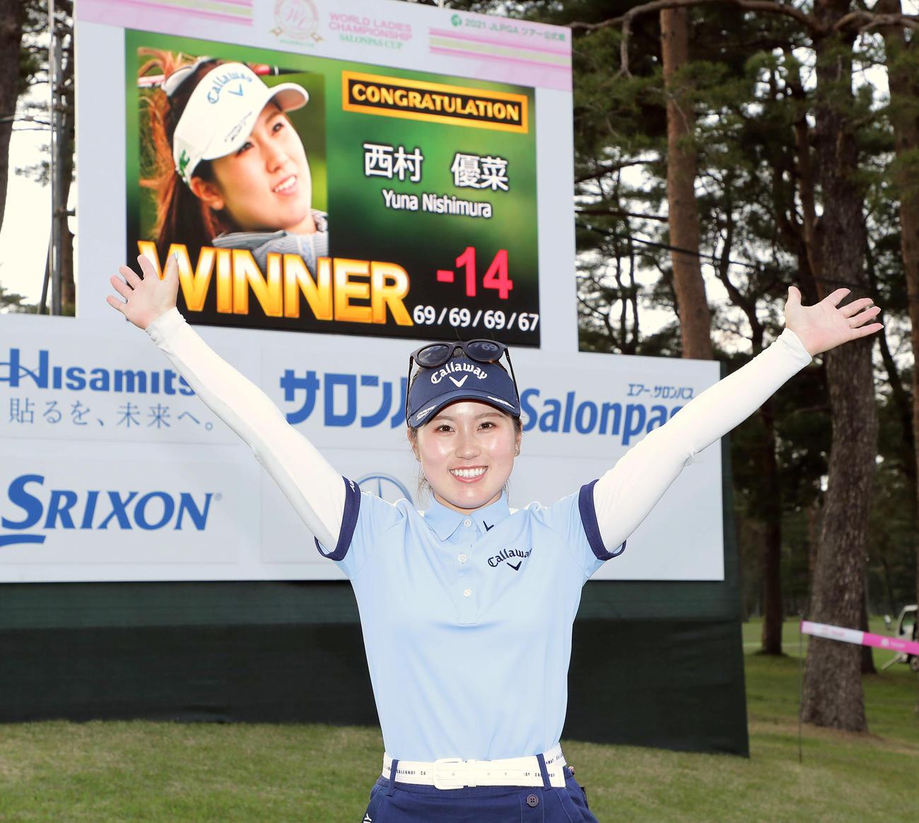 初の国内メジャー制覇を果たし、フォトセッションで万歳する西村(撮影・河田真司)