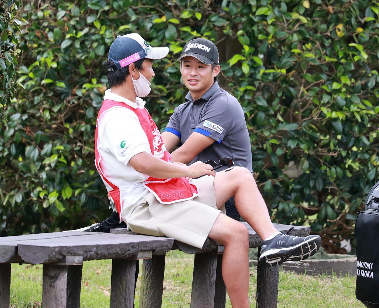 13番、ティーを待つ間、ベンチでリラックスした表情でキャディーと談笑する片岡(撮影・浅見桂子)