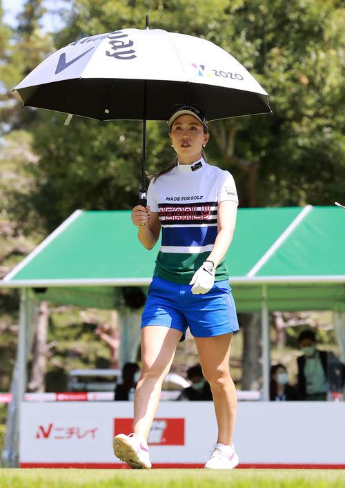 1番、ティーショット後、傘をさして歩き出す上田(撮影・浅見桂子)