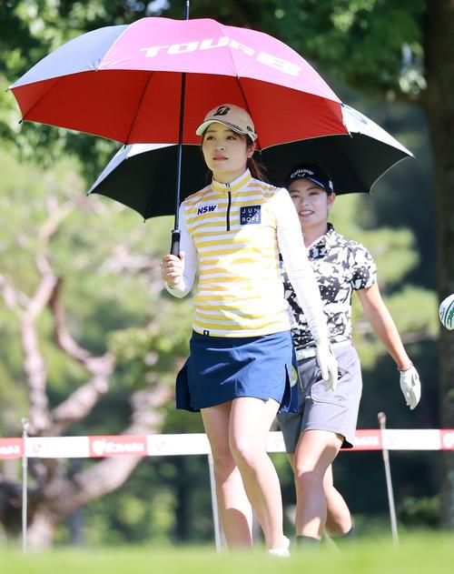 1番、ティーショット後、傘をさして歩き出す三ケ島(撮影・浅見桂子)