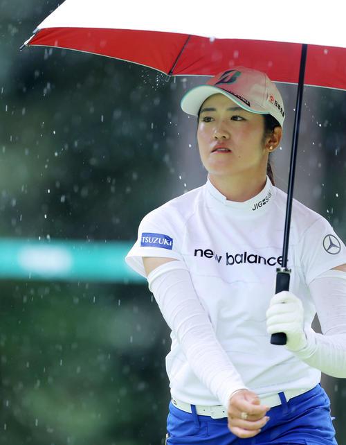 12番、雨が降りだし、傘を差しながら移動する稲見(撮影・河田真司)