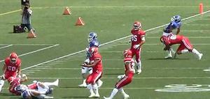 第1Q、ボールを投げ終わった関学大QB(右後方の青ユニホーム)の背後から、日大DL(同赤ユニホーム)がタックルを仕掛ける(6日、関学大提供)