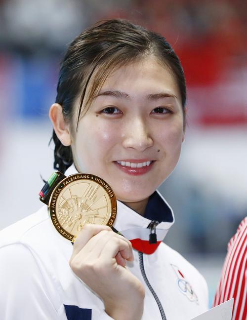 女子100メートル自由形で優勝し、メダルを手に笑顔の池江(共同)=2018年8月20日