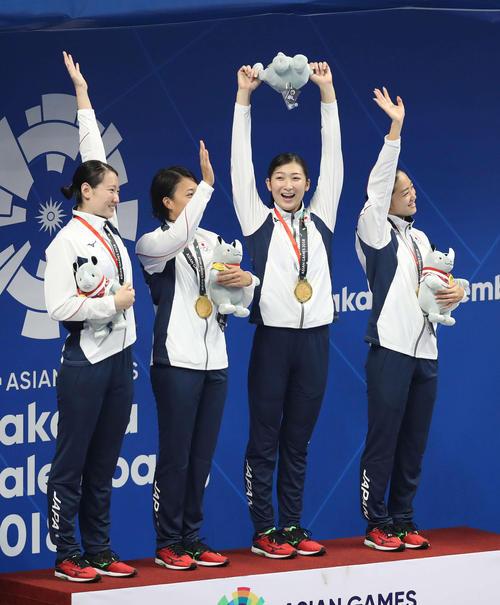女子400メートルメドレーリレーで優勝し表彰式でマスコット人形を高く掲げる池江(左から3人目)。左から酒井、鈴木、1人おいて青木(撮影・河野匠)2018年8月23日