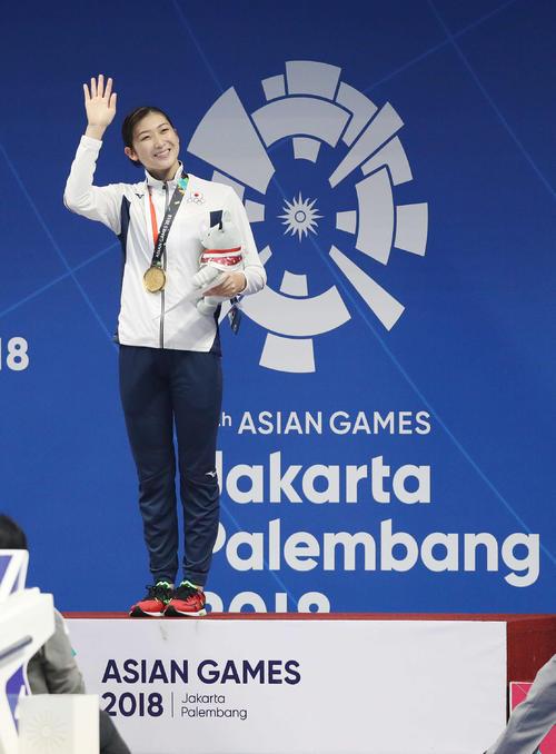 女子100メートルバタフライで優勝し表彰式で笑顔を見せる池江(撮影・河野匠)=2018年8月21日
