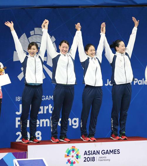 女子400メートルリレーで3分36秒52の日本新記録で優勝し表彰台に笑顔で上がった池江、酒井、青木、五十嵐の日本チーム(撮影・河野匠)=2018年8月19日