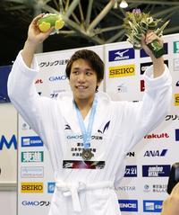 男子200メートル自由形で優勝し、表彰台で手を振る松元(共同)