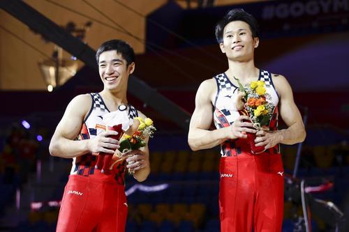 男子個人総合決勝を終え、表彰式で笑顔の6位の萱和磨(右)と7位の白井健三(共同)
