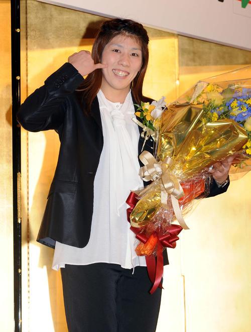 受け取った花束を手に笑顔でポーズを決める吉田(2012年撮影)
