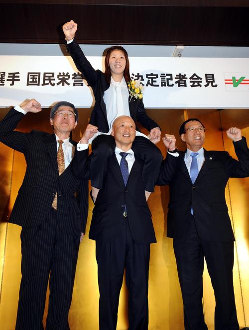国民栄誉賞受賞が決まった吉田(上)は、日本レスリング協会の栄女子強化委員長(中央下)に肩車され、力強くガッツポーズをつくった(2012年撮影)