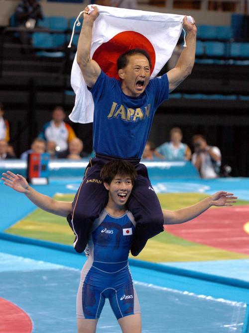 女子55キロ級決勝で金メダルを決め、中京女大の栄監督を肩車して喜ぶ吉田沙保里(2004年撮影)