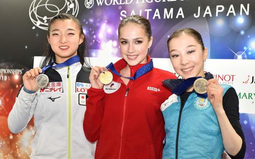 女子SPを終え、ミニメダルを手に笑顔を見せる、左から2位の坂本、1位のザギトワ、3位のトゥルシンバエワ(撮影・鈴木みどり)