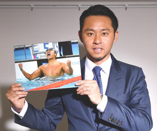 北京五輪100メートル平泳ぎで優勝し雄たけびを上げる自身の写真を手にする北島康介氏