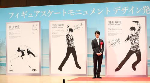 新たなモニュメントのデザイン画(右)や荒川静香さんのデザイン画(左)とともに記念撮影におさまる羽生結弦(撮影・林敏行)