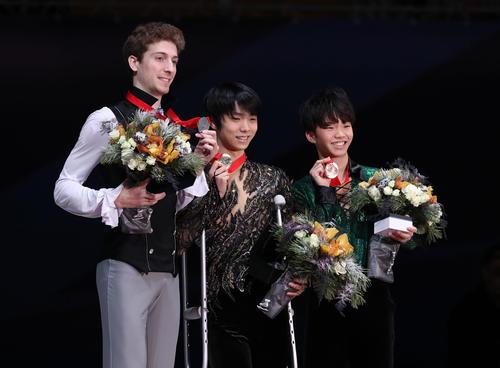 表彰式で松葉づえを手に笑顔を見せる羽生(中央)。左は2位のクビテラシビリ、右は3位の友野(2018年11月18日撮影)