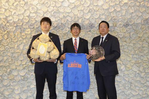 高見副市長(中央)に今季の報告を行い、記念撮影をする石井(左)と小菅社長
