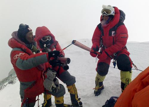 08年5月、チョモランマの頂上直下で北京五輪聖火の火種からトーチに点火する登山隊員(新華社=共同)
