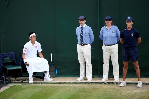 急病人処置のため試合が一時中断となり、ラインズマンのイスに座る錦織(ロイター)