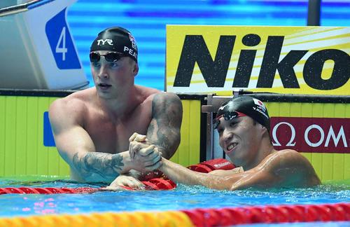 男子00メートル平泳ぎ準決勝で世界新を出したピーティー(左)と握手を交わす小関(撮影・鈴木みどり)