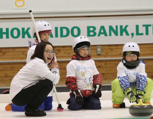 子どもたちと一緒にストーンを見つめるロコ・ソラーレの藤沢(左端)(撮影・西塚祐司)
