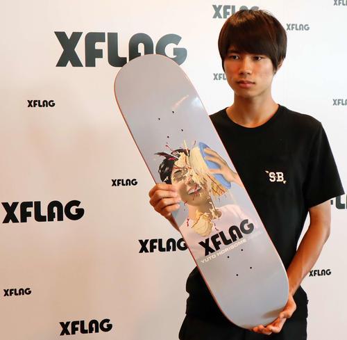 プロの証でもある自らの名を冠したボードを手にするスケートボードの堀米雄斗