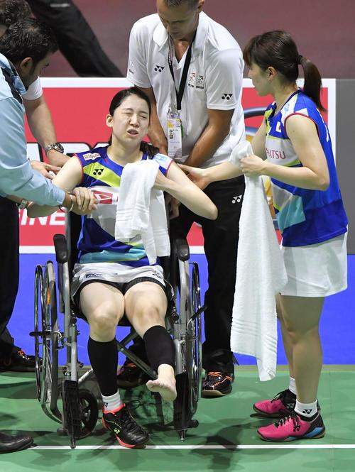 女子ダブルス準々決勝 永原、松本組との対戦中に左足首付近を負傷し、車いすで退場する米元。右は田中(共同)