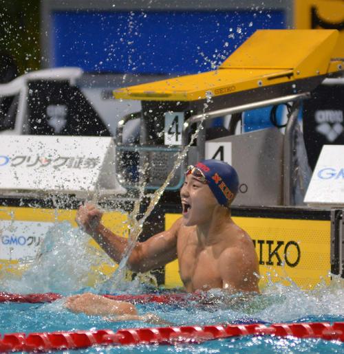 男子200メートル平泳ぎで優勝し、水面をたたいて喜ぶ佐藤翔馬(撮影・吉池彰)