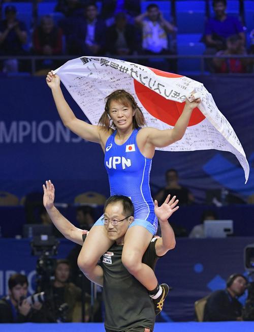 女子57キロ級で優勝し、肩車で日の丸を掲げる川井梨(共同)