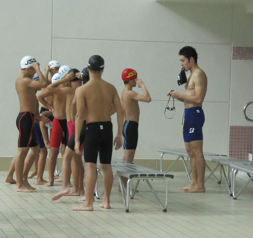 萩野(右)は、予選同組となった小学生に敬礼であいさつされた(撮影・益田一弘)