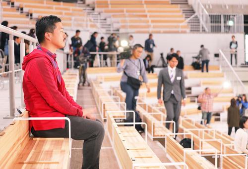 有明体操競技場の木製観客席の座り心地を確かめる本紙の阿部記者(撮影・河田真司)