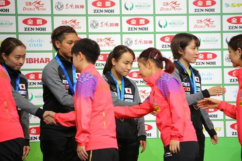 表彰式で優勝した中国代表チーム(手前)と握手を交わす準優勝の日本代表チーム(撮影・河田真司)