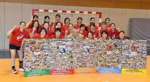 ファンからボードを受け取り、笑顔で記念写真に納まるハンドボール女子日本代表(撮影・鈴木みどり)