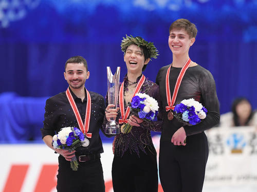 NHK杯 男子シングルスで優勝を決め、表彰式で笑顔を見せる羽生(中央)。左は2位エイモズ、右は3位サドフスキー(撮影・加藤諒)