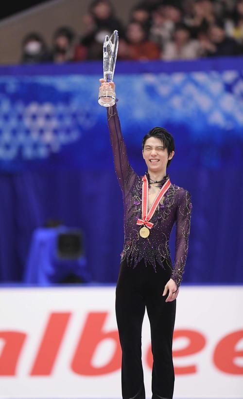 男子シングルスで優勝を決め、表彰式でトロフィーを掲げる羽生(撮影・加藤諒)