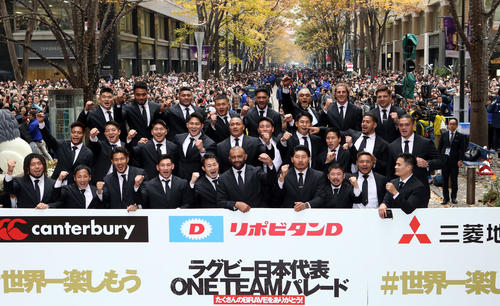 多くのサポーターの前でパレードを行った後、記念撮影をするリーチ(前列中央)ら日本代表の選手たち(撮影・狩俣裕三)