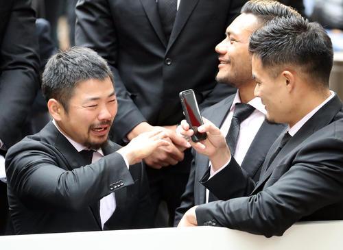 パレード中、泣きっぱなしの田中(左)を撮影する田村(撮影・狩俣裕三)