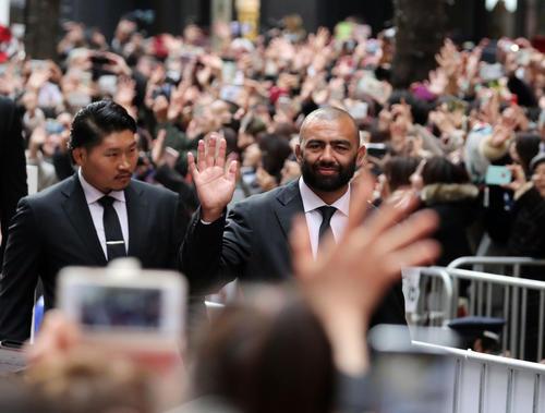 「ラグビー日本代表ワンチームパレード」で沿道のファンに笑顔で手を振るリーチ(右)と稲垣(同2人目)(撮影・垰建太)