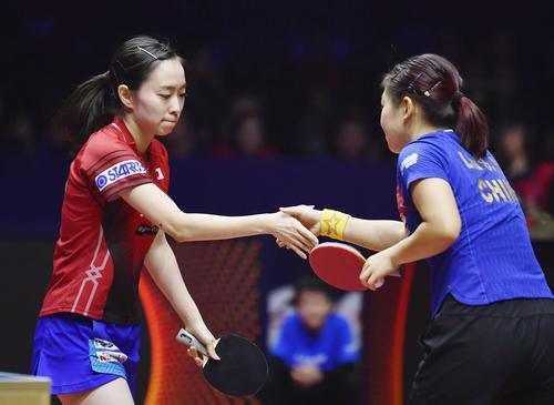 女子シングルス1回戦で劉詩文 (右)に敗れ、握手を交わす石川佳純(共同)