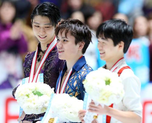 男子フリーの表彰式で優勝した宇野(中央)を見つめてほほ笑む2位の羽生(左)。右は3位鍵山(撮影・垰建太)