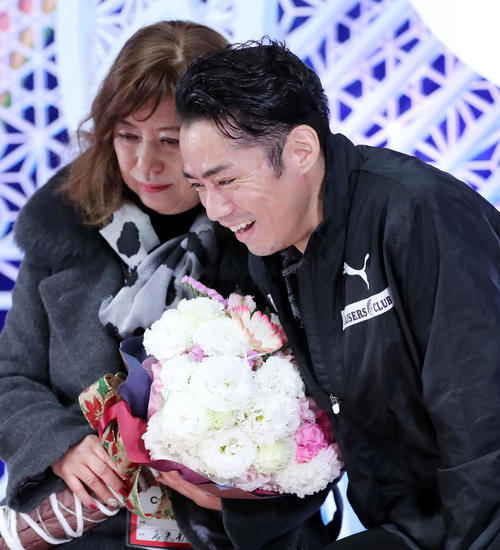 男子フリーの演技を終えた高橋大輔(右)は長光歌子コーチに花束を渡し笑顔を見せる(撮影・垰建太)