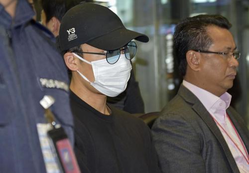 マスク姿で空港に到着したバドミントン男子の桃田賢斗(中央)(共同)