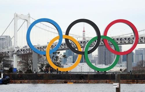 東京タワーとレインボーブリッジをバックに、お台場海浜公園付近の海上に到着した五輪シンボル(撮影・大野祥一)