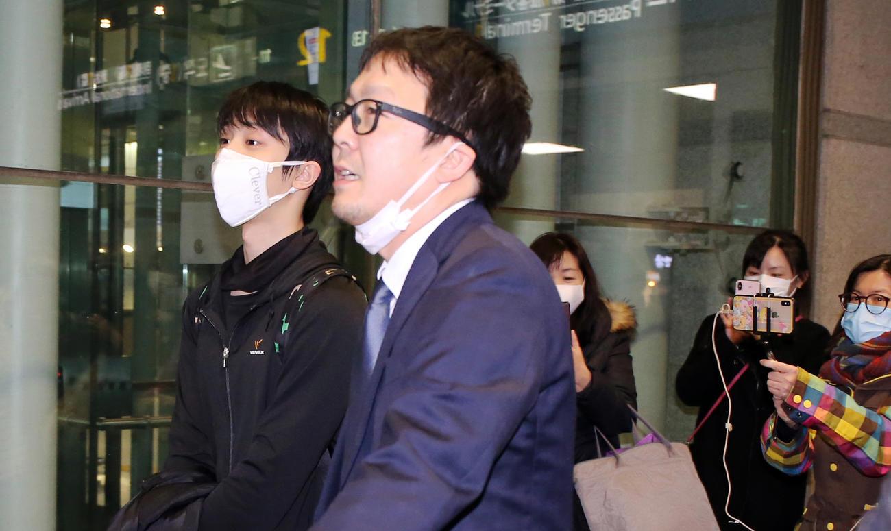 韓国の仁川国際空港に到着した羽生は、集まったファンから守られて車に向かう(撮影・浅見桂子)